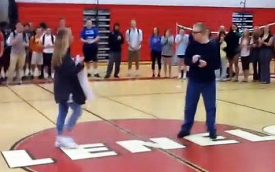 She Walks Over To Him On The Court With a Sign. The Sign Leaves Everyone Cheering!